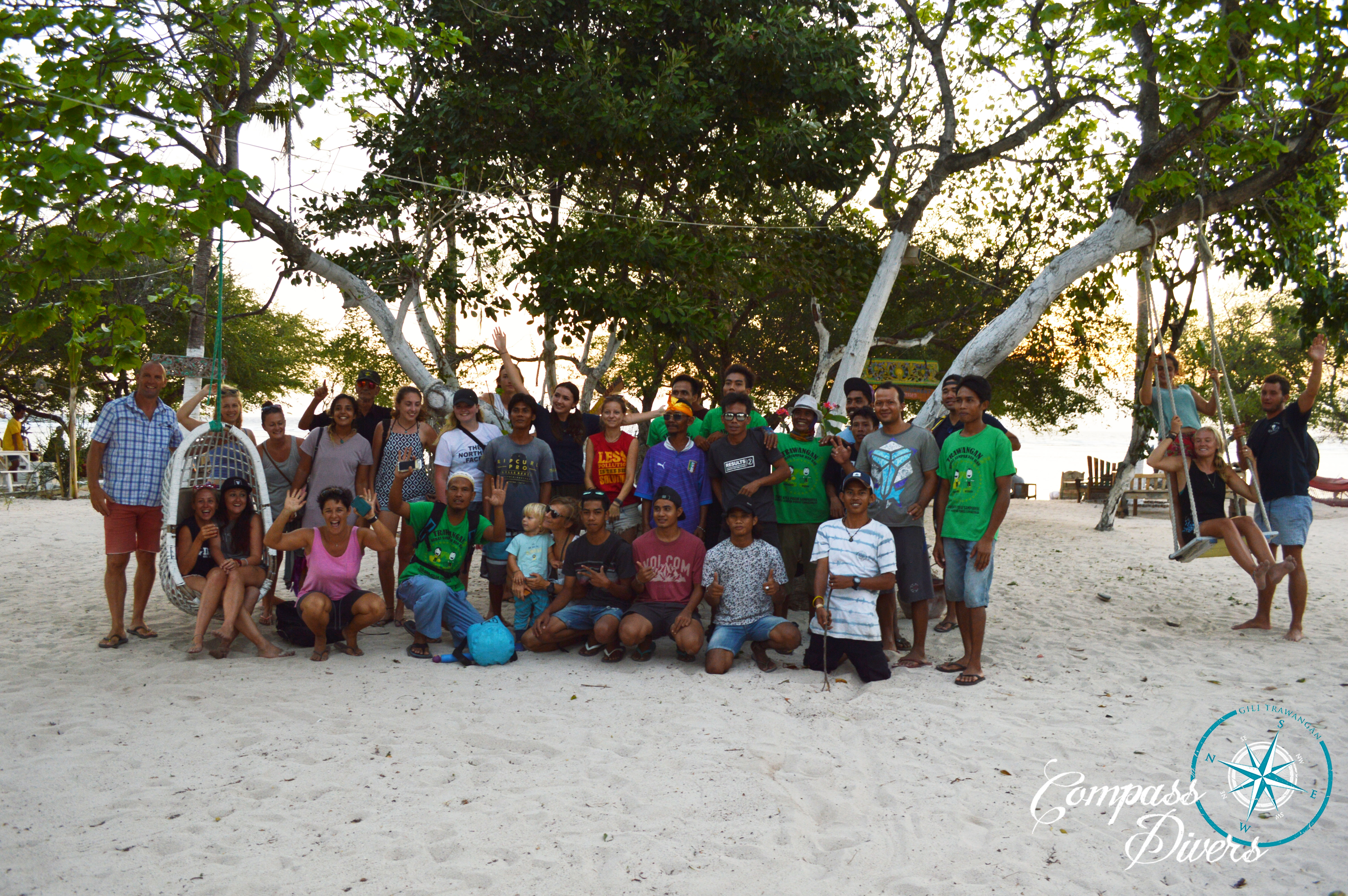 A group of people on the beach celebrating their beach clean up.
