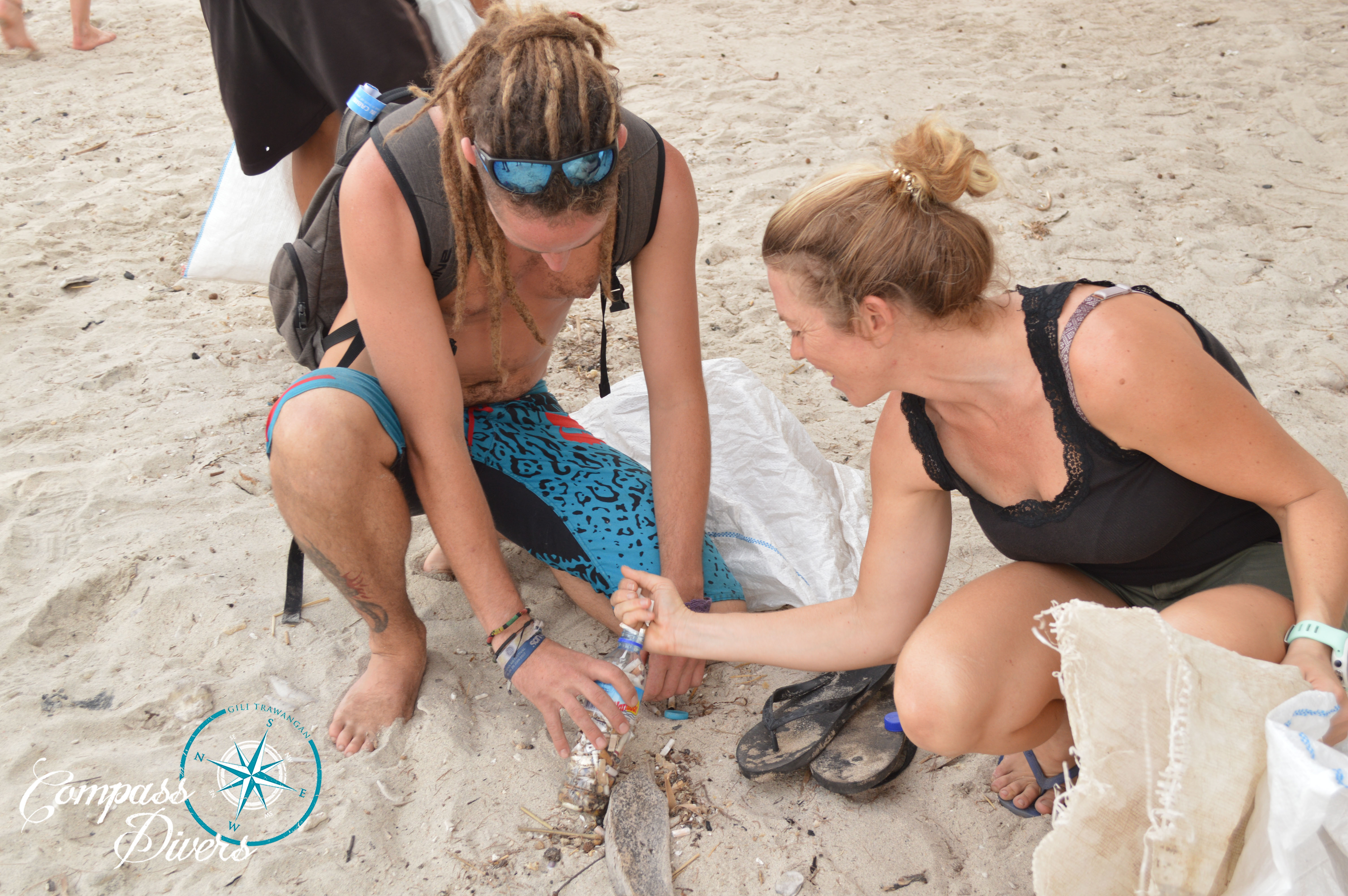 A couple help to clean cigarette butts up off the beach.