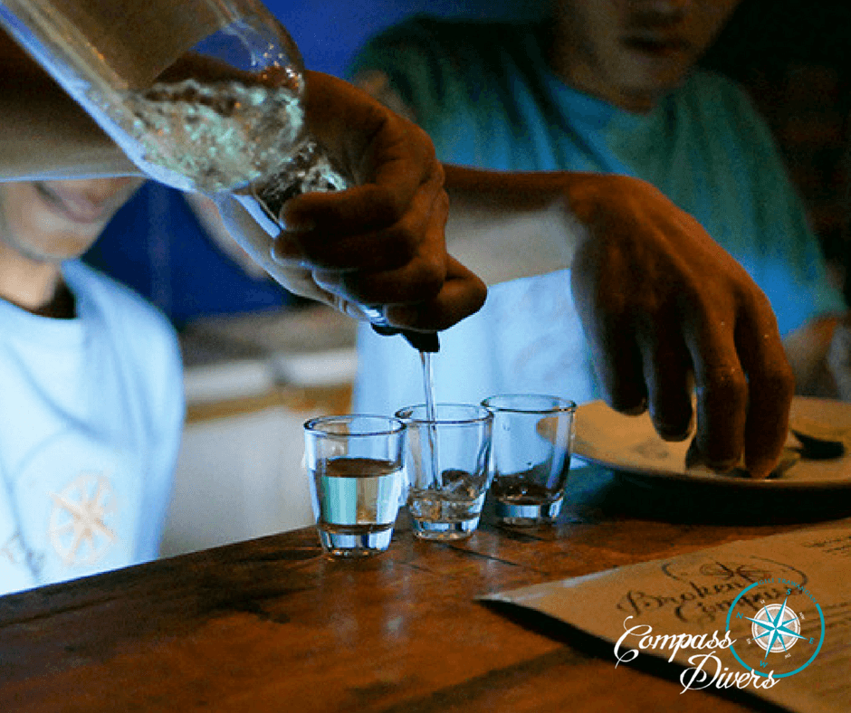 Bar staff pouring tequila into three shot glasses.