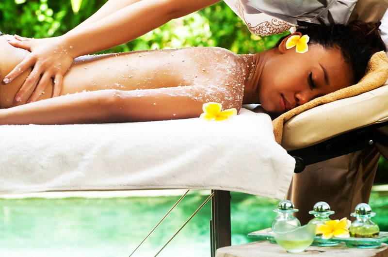 Woman laying on her front on massage bed, surrounded by nature.